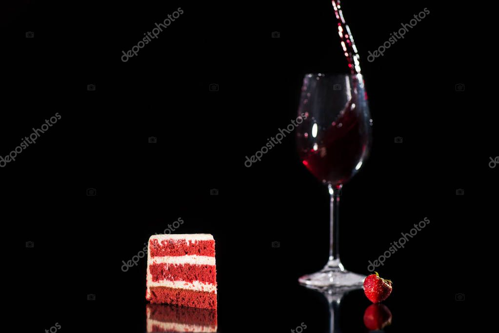 Piece of red and white cake near glass of wine isolated on black stock vector