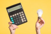 cropped view of woman holding fluorescent lamp and calculator in hands isolated on yellow, energy efficiency concept