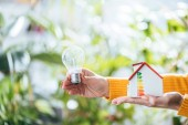 Photo selective focus of led lamp and carton house model in woman hands, energy efficiency at home concept