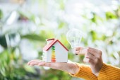 Photo cropped view of woman holding led lamp and carton house, energy efficiency at home concept