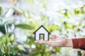 Photo cropped view of paper house in hand of man, energy efficiency at home concept