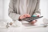 oříznutý pohled ženy pomocí kalkulačky poblíž lampy na bílém pozadí, koncepce energetické účinnosti