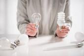 abgeschnittene Ansicht einer Frau mit LED- und Leuchtstofflampen auf weißem Hintergrund, Energieeffizienzkonzept