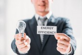 Photo selective focus of card and led lamp in male hands of businessman on white background, energy efficiency concept