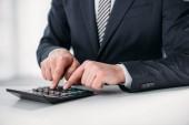 oříznutý pohled podnikatel v obleku pomocí kalkulačky na bílém pozadí, koncepce energetické účinnosti
