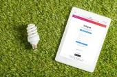 pohled shora na zářivku poblíž digitální tablet s aplikaci instagram na obrazovce na zelené trávě, koncepce energetické účinnosti