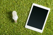 Fotografie top view of fluorescent lamp near digital tablet with blank screen on green grass, energy efficiency concept