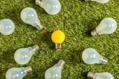 Fotografie top view of fluorescent lamps near yellow lamp on green grass, energy efficiency concept