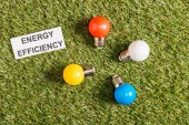 Fotografie top view of colorful fluorescent lamps near paper card with lettering on green grass, energy efficiency concept