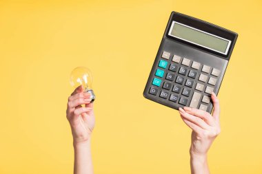 cropped view of woman holding led lamp and calculator in hands isolated on yellow, energy efficiency concept