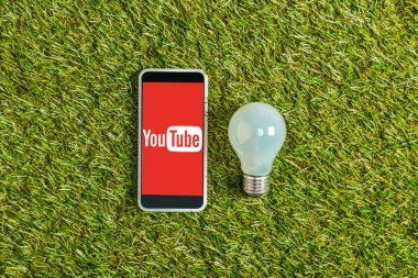 top view of fluorescent lamp near smartphone with youtube app on screen on green grass, energy efficiency concept