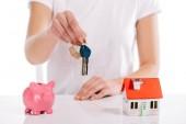 Fotografia vista parziale della donna che tiene le chiavi vicino casa modello e banca piggy isolato su bianco, concetto di ipoteca