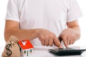 Fotografia partial view of man calculating near moneybag and house model isolated on white, mortgage concept