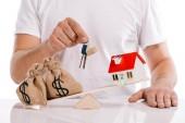 Fotografie částečné zobrazení člověka drží klíče u modelu pracháč a dům na váhách izolovaných na bílém, hypoteční koncepce