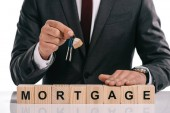 Fotografie cropped view of businessman holding keys near wooden cubes with mortgage lettering isolated on white