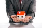 Fotografie oříznutý pohled hypoteční makléř drží dům modelu izolované na bílém