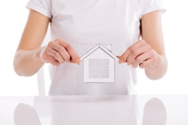 Partial view of woman holding paper house isolated on white, mortgage concept stock vector