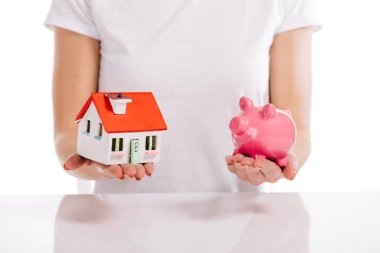 partial view of woman holding house model and piggy bank isolated on white, mortgage concept