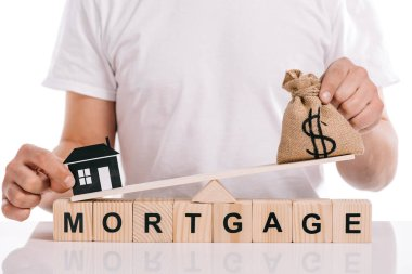 cropped view of man holding moneybag and paper house on scales on cubes with mortgage lettering isolated on white