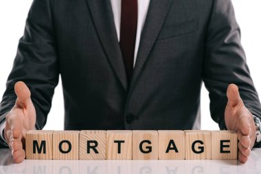 cropped view of businessman holding wooden cubes with mortgage lettering isolated on white