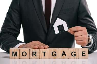 cropped view of mortgage broker holding paper house near wooden blocks isolated on white
