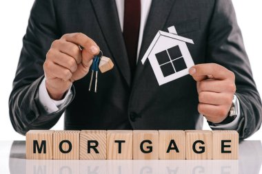 cropped view of mortgage broker holding paper house and keys near wooden blocks isolated on white