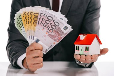 cropped view of businessman holding house model and euro banknotes isolated on white, mortgage concept