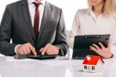 selektiver Fokus des Hausmodells mit Geschäftsleuten mit Taschenrechner und Klemmbrett isoliert auf weißem Hypothekenkonzept