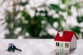 messa a fuoco selettiva delle chiavi e modello della casa sulla scrivania bianca, concetto di ipoteca