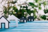 Selektivní fokus papíru domy na modré dřevěný stůl, hypoteční koncepce