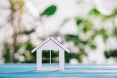 Photo selective focus of paper house on blue wooden desk, mortgage concept