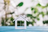 Selektivní fokus papíru domu na modré dřevěný stůl, hypoteční koncepce