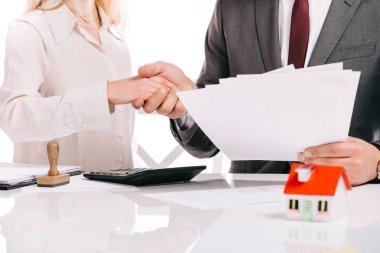 cropped view of businessman and businesswoman shaking hands and holding papers isolated on white, mortgage concept