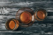 Fotografie top view of bottled organic tea on wooden table