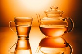 selective focus of cup of tea and teapot on orange background