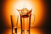 Fotografie Selektivní fokus skla a konvici s čajem a citron na pozadí