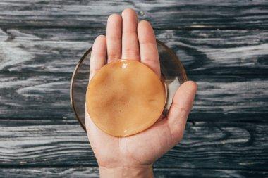 Top view of man holding kombucha mushroom in hands stock vector