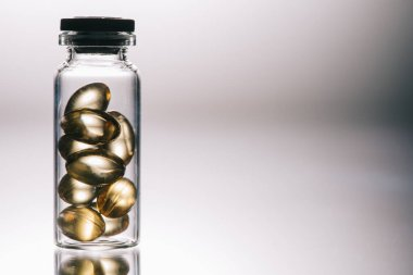 medical pills with transparent shell in bottle on grey background