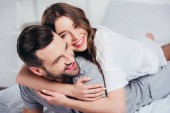 selective focus of young loving couple hugging and smiling in bed