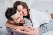 Selektivní fokus mladých milující pár objímat a usmíval se v posteli
