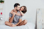 Fotografie adult couple hugging and sitting on bed with white bedding