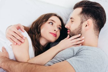 young loving woman gentle looking in eyes of man in bed
