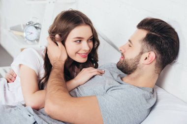 loving couple gentle embracing and looking in eyes of each other in bed