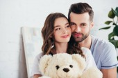 selective focus of happy couple embracing teddy bear