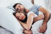 felnőtt pár alszik a hálószobában puha fehér ágynemű