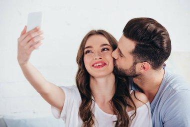 Boyfriend kissing girlfriend while taking selfie in bedroom stock vector