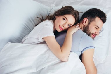 young loving girlfriend gentle embracing boyfriend in bed