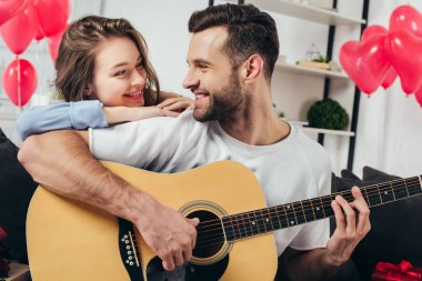 young man playing acoustic guitar while smiling girlfriend leaning on his shoulder