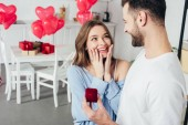 Photo selective focus of surprised girl touching face while man doing proposal at valentines day