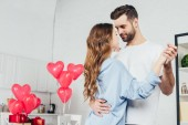 Photo happy couple dancing at home in room decorated with heart-shaped balloons